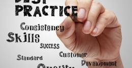 a hand writing words like best practice, skills, success